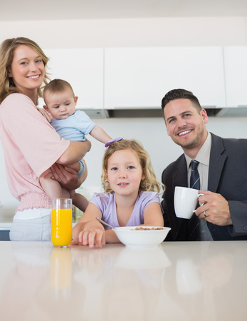 Portrait of family at breakfast table in house photo