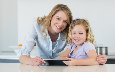 Portrait of happy mother and daughter holding digital tablet at table in house photo