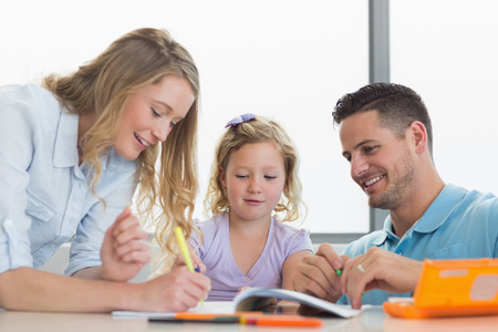 Happy parents assisting daughter in drawing at table in house photo
