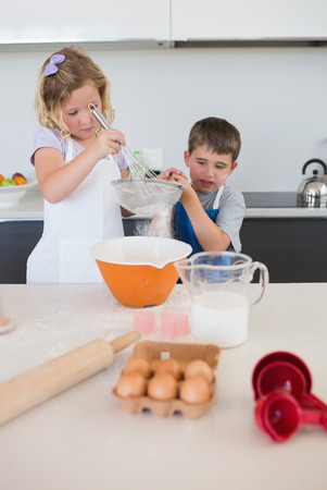 Children baking cookies together at kitchen counter photo
