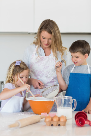 Children with mother baking cookies at counter top in kitchen photo