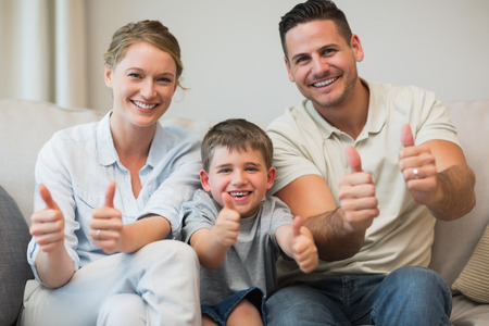casuals: Portrait of happy family gesturing thumbs up while sitting on sofa at home