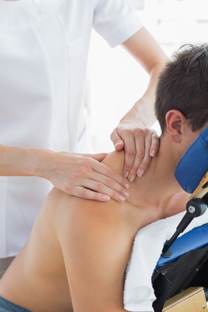 female therapist: Man receiving shoulder massage by female therapist in hospital