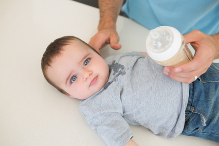 High angle portrait of innocent baby boy with father feeding milk at counter photo