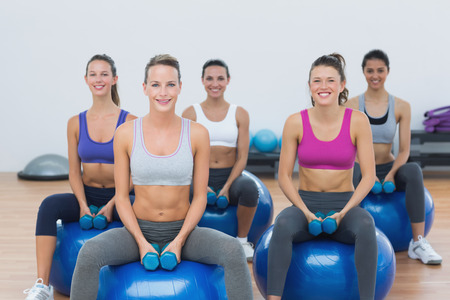 Smiling young women exercising with dumbbells on fitness balls in gym photo