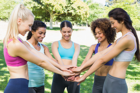 Fit young women stacking hands together in the park Stock Photo
