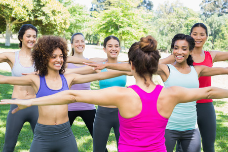 group fitness: Happy women exercising with female instructor at park