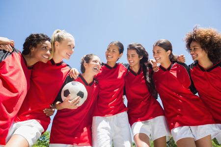 Gelukkig vrouwelijke voetbalteam met bal tegen de heldere blauwe hemel