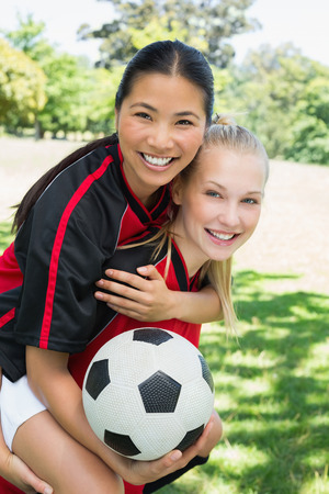 teammate: Portrait of happy female soccer player piggybacking teammate at park