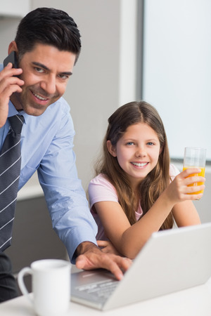 Portrait of a smiling father with young daughter using laptop in the kitchen at home photo