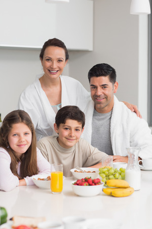 Portrait of happy young kids enjoying breakfast with parents in the kitchen photo