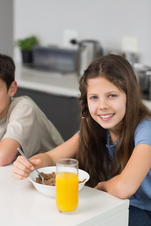 Portrait of two smiling young siblings enjoying breakfast in the kitchen photo
