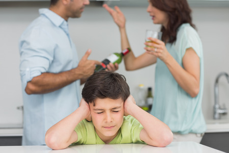 Sad young boy covering ears while parents quarreling in the kitchen at home photo