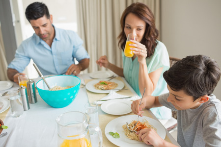 High angle view of family of three sitting at dining table in the home