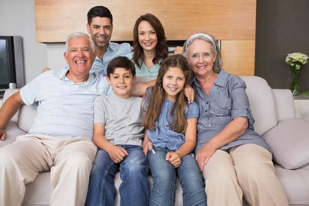 Portrait de sourire famille élargie assis sur un canapé dans le salon à la maison