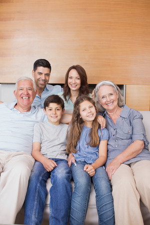 Portrait of smiling extended family sitting on sofa in the living room at home photo