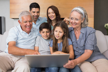 Happy extended family using laptop on sofa in the living room at home photo