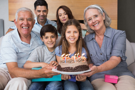 Portrait of extended family sitting on sofa with cake in the living room at home photo