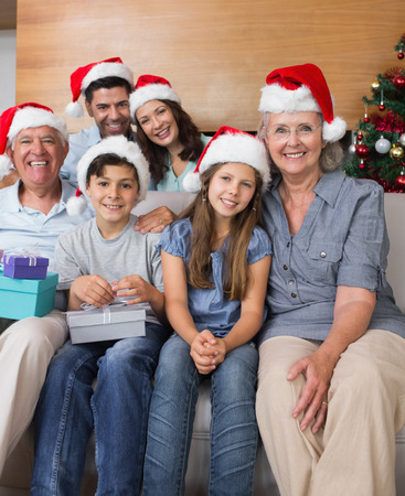 Portrait of extended family in Christmas hats with gift boxes in the living room at home photo