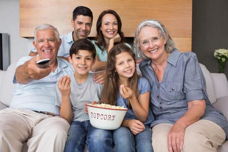 personas viendo television: Retrato de la feliz familia viendo la televisi�n en el sof� en la sala de estar en casa