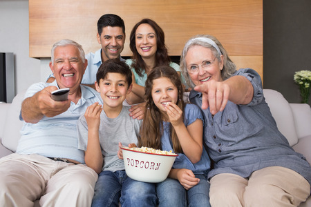 Portrait of happy extended family watching tv on sofa in the living room at home photo