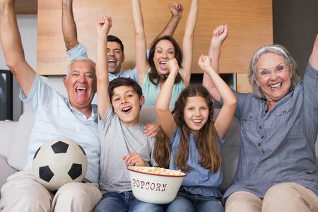 Portrait eines gl�cklichen Gro�familie vor dem Fernseher auf dem Sofa im Wohnzimmer zu Hause
