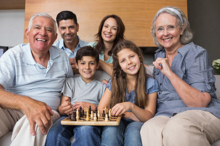 Portrait of happy extended family playing chess on sofa in the living room at home photo