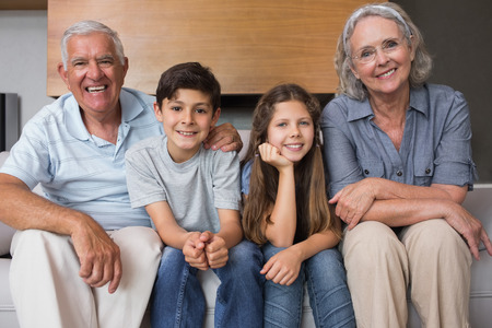 Portrait of grandparents and two kids sitting on sofa in the living room at home photo