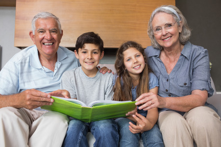 Portrait of happy grandparents and grandkids looking at album photo in the living room photo