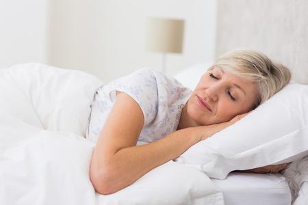 gente durmiendo: Mujer bastante madura durmiendo con los ojos cerrados en la cama Foto de archivo