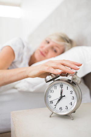 extending: Blurred sleepy mature woman extending hand to alarm clock in bed at home Stock Photo