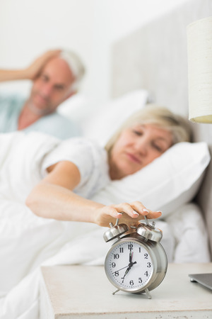 Blurred sleepy mature woman extending hand to alarm clock in bed at home photo