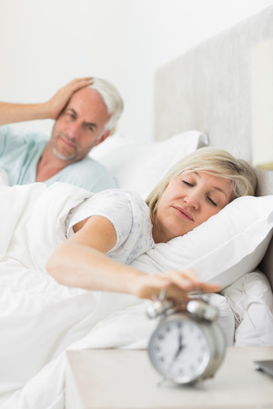 Man covering ears while woman extending hand to alarm clock in bed at home photo
