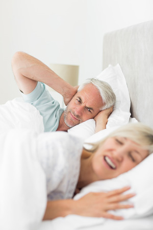 Closeup of a man covering ears while woman shouting in bed at home photo