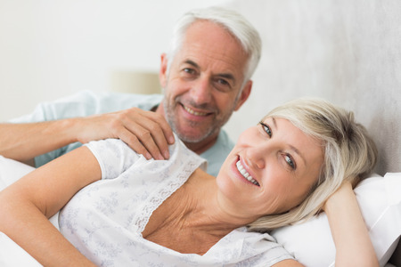 Closeup portrait of a smiling woman and mature man lying in bed at the home photo