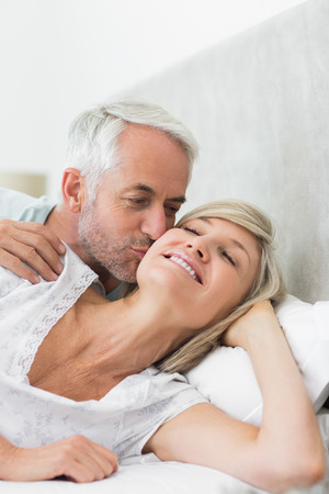 Closeup of a mature man kissing womans cheek in bed at the home photo