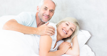 Portrait of a smiling woman and mature man lying in bed at the home photo