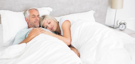 pareja en la cama: Hombre maduro cari�oso y la mujer acostada en la cama en la casa