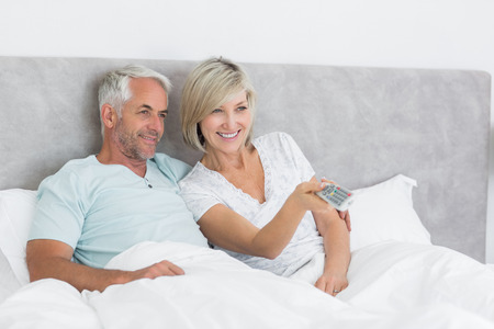 Happy mature couple watching tv in bed at home photo
