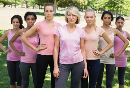 Portrait of confident women supporting breast cancer awareness at park photo