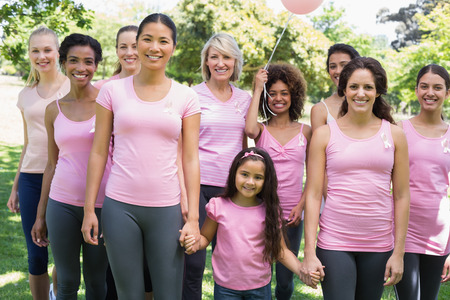 Portrait of confident multiethnic women and girl supporting breast cancer awareness at park photo