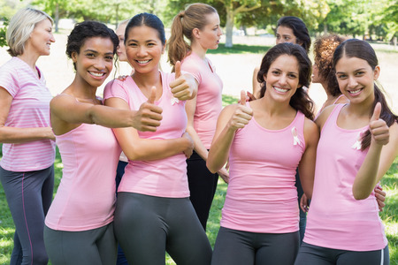 Portrait of happy female breast cancer participants gesturing thumbs up during campaign at park photo