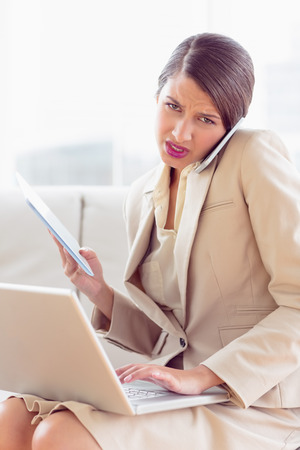 multi tasking: Busy and stressed businesswoman sitting on sofa multi tasking in the office Stock Photo