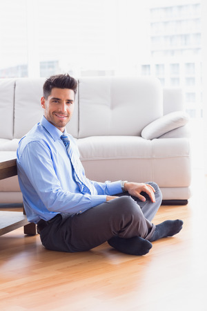 Handsome businessman sitting on the floor in the office Stock Photo