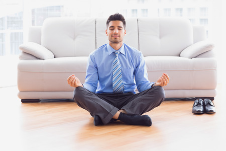 Businessman meditating in lotus pose on the floor in the office photo