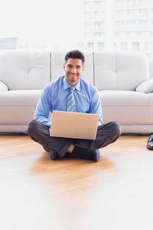 Businessman sitting on floor using his laptop smiling at camera in the office photo