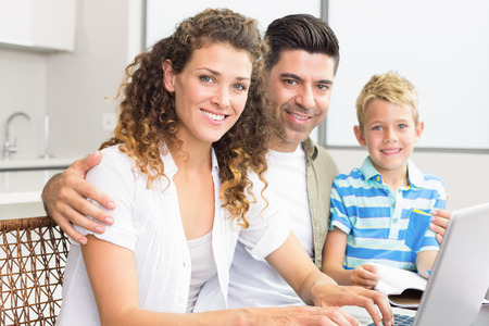 Cute little boy using laptop with parents at table at home in kitchen photo