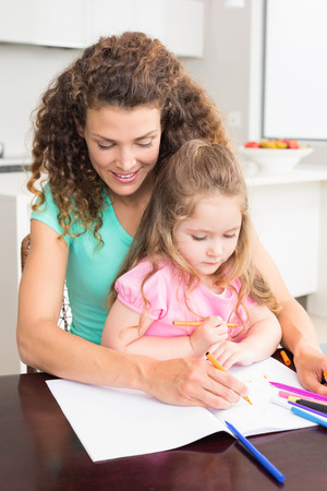 Mother and daughter colouring together at the table at home in kitchen photo
