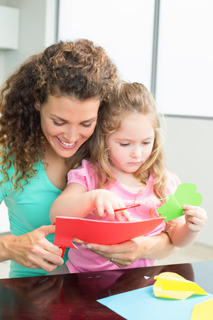 Happy little girl cutting paper shapes with mother at the table at home in kitchen photo