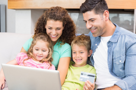 Happy family sitting on sofa using laptop together to shop online at home in living room photo